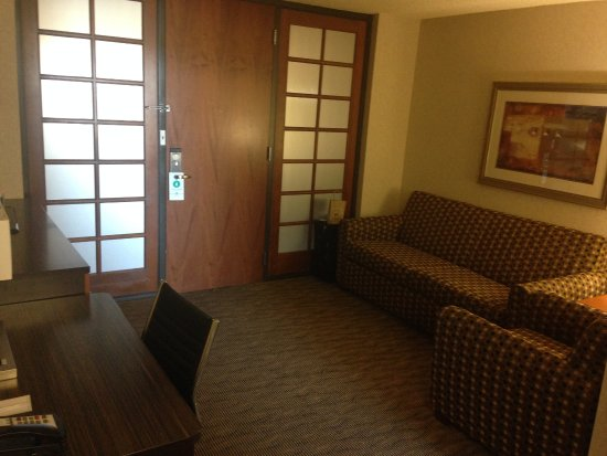Embassy Suites by Hilton Oklahoma City Will Rogers Airport: Entrance to room and couch and chair.