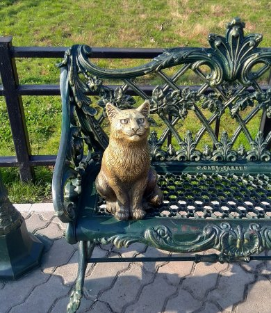 the sculptural composition unflappable cat cat sitting on a bench
