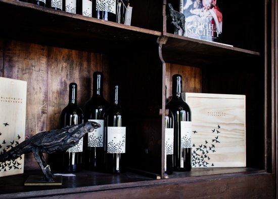 Antique bookshelf displaying objet d art and Blackbird Vineyards