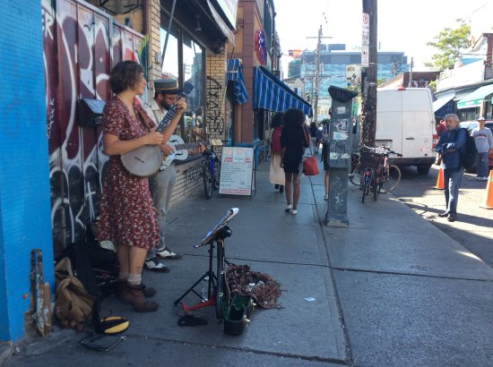 Kensington Market and Spadina Avenue: A young couple entertaining people with songs and music