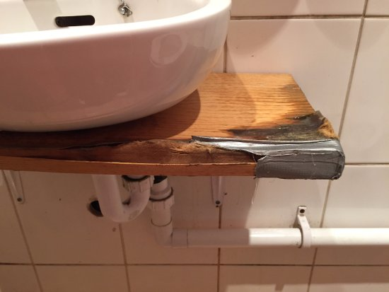 Soaking Wet Rotting And Mouldy Sink Shelf In Bathroom