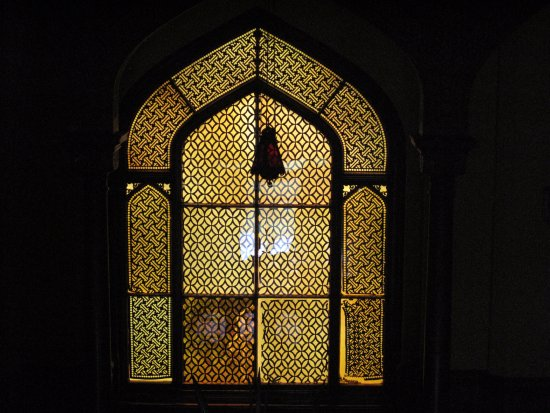 Amber glass window with designs made of paper between the glass ...