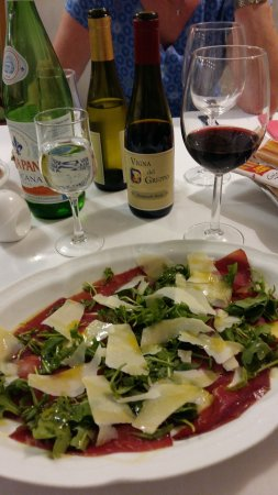 Province de Lucques, Italie : Starter of beef with paresan, rocket and olive oil. Half bottles of wine