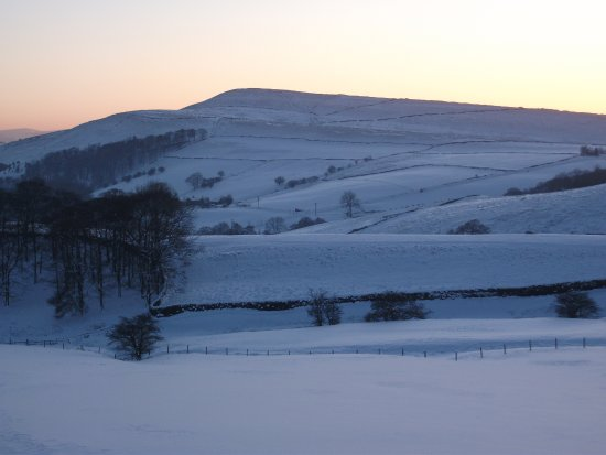 Little Hayfield, UK: Snowy Winter scene showing the Lantern Pike hill