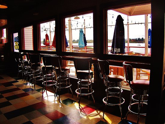 Vancouver, WA: stools in the bar lined up at windows with view of the patio