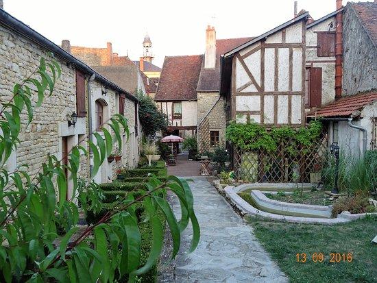 Le Relais Fleuri : A l'arrière du relais la cour intérieure. Le dîner est servi en terrasse à l'avant de la photo.