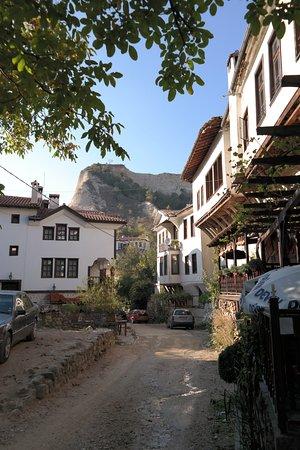Melnik, Bulgarien: Rechts die Veranda der Mencheva Kashta. Restaurierte Wiedergeburtshäuser säumen die schmale Stra