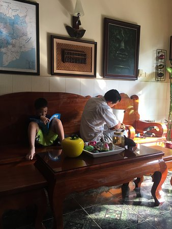 Fancy Guest House: Phannak works hard on repairs whilst his son studies his English Homework.