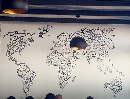 Carte du monde en calligraphie arabe peinte sur le mur par l