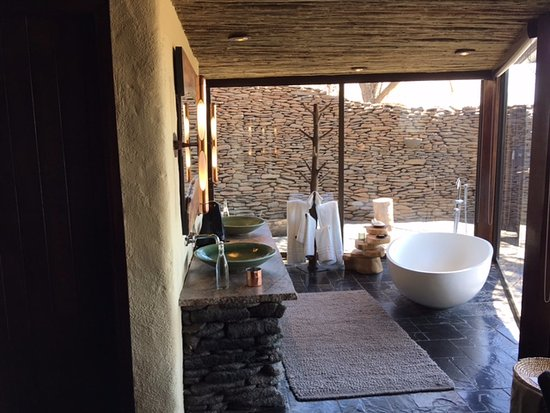 Singita Boulders Lodge: The bathroom with an outdoor shower in the background to the right