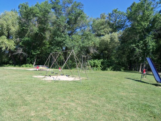 Mequon, WI: Retro vintage Playground, with a metal slide, metal merry go round, and vintage jungle gym