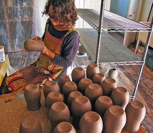 Beach, ND: North Dakota pottery Tama Smith applying handles to handmade mugs.