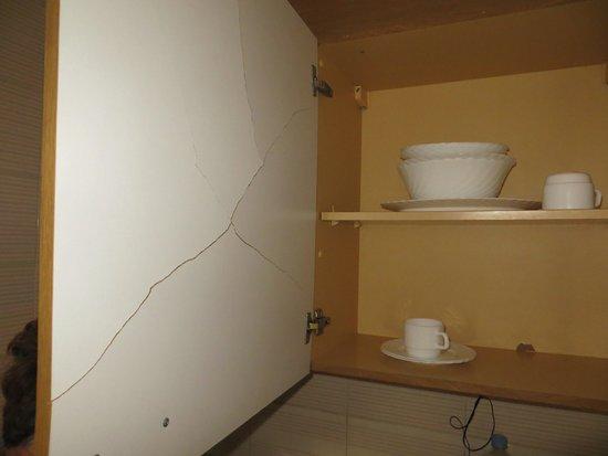 """Bora Bora Apartments: Het """"keukengerei"""" en de kastdeur vol scheuren. Er was ook nog wat bestek."""
