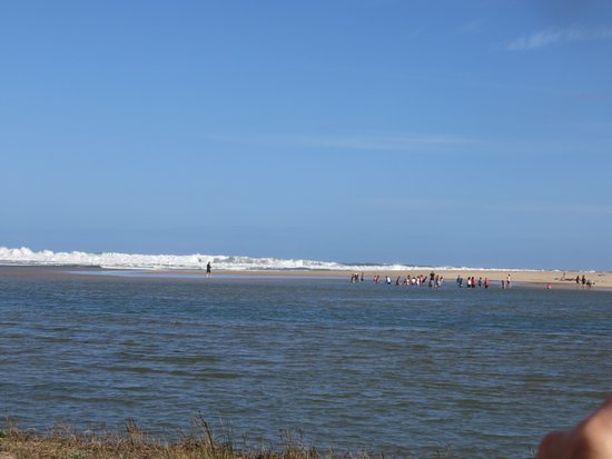 George, South Africa: The open sea viewed from the island with children playing on the lagoon beach with waves breakin