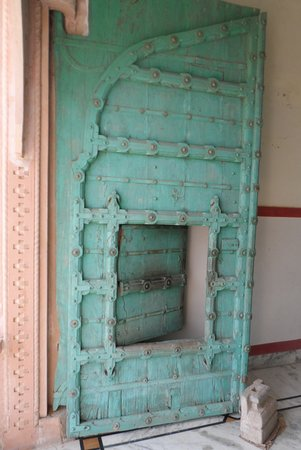 Malpura, Indie: Entrance well aged metal studded wooden doors washed in aqua blue