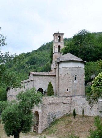 Preci, Italy: L'ingresso, con l'abside e il campanile
