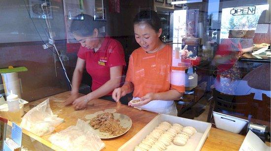 Friendly staff making pork pot stickers