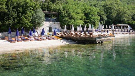 Perast, Montenegro: вид с маленькгого причала для лодок. между деревьями виднеется площадка ресторана