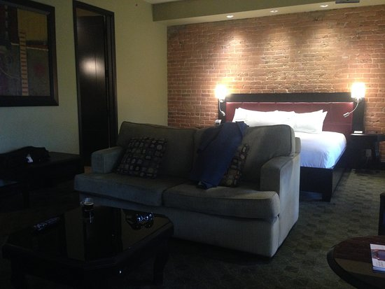 Le Place d'Armes Hotel & Suites: Exposed brick wall, king-size bed, comfy sofa...Room 2202