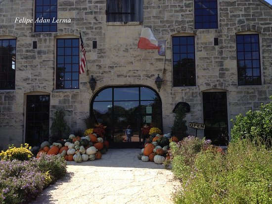 Stonewall, TX: Entrance door to Becker Vineyards topped with Texas and US flags plus piles of pumkins.