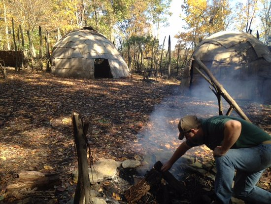 Avella, PA: The docent preparing a fire in the re-creation of a 15th century Native American village.