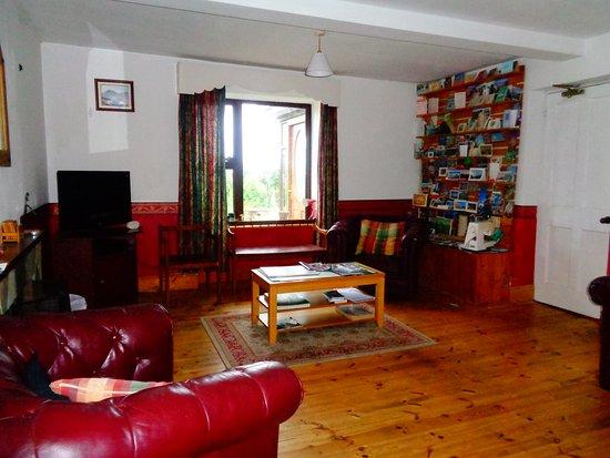 Donegal Town Independent Hostel: sala comune con due divani e una poltrona e tanti leaflets per prendere idee