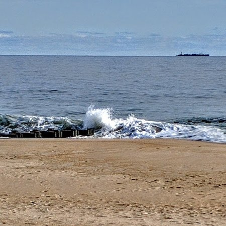 Waves crashing on the jetties with a ship in the for Rehoboth beach fishing