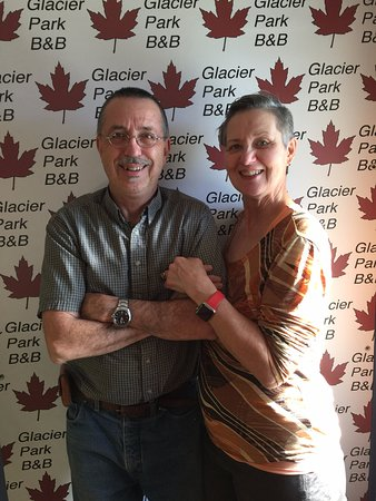 Glacier Park Bed and Breakfast: Your hosts, Bill and Deb in Front of the new GPBB Banner
