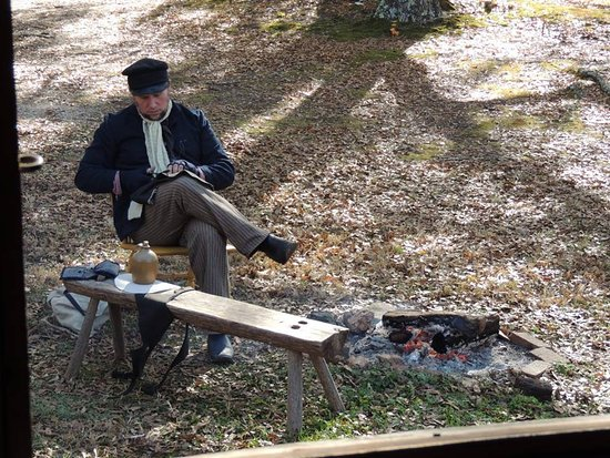 McConnells, SC: A volunteer makes hats from leather while enjoying a drink next to the warm fire.