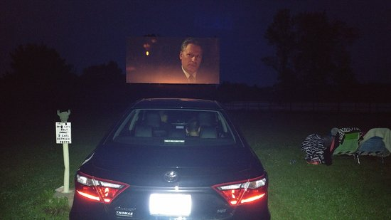 Big Sky Drive In : Drive in with people sitting outside next to the car