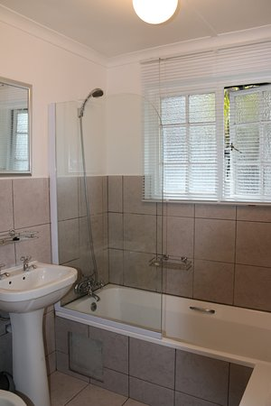 George Lodge International: En-suite bathroom with bath and shower over bath