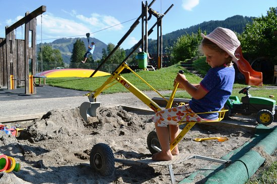 Saanen, Schweiz: Der Sandkasten mit Bagger auf dem Spielplatz.