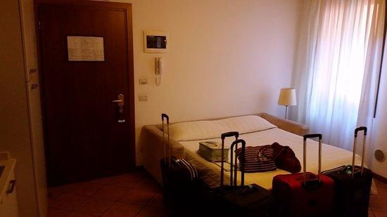 Residence Corte Grimani: Porta do quarto com o sofá cama. À esquerda, a pequena copa com fogão, pia e frigobar.