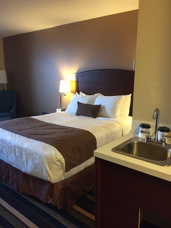 fortable bed and small bar sink with coffee maker beside bathroom