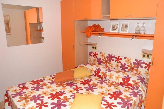 Finale, Italy: Camera da letto matrimoniale nella casa mobile con angolo cottura