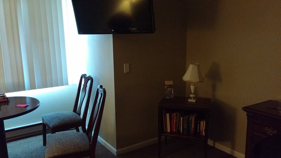 East Shore Lodging: Wall mounted TV, book rack and table with chairs in the 2 Queen accessible room
