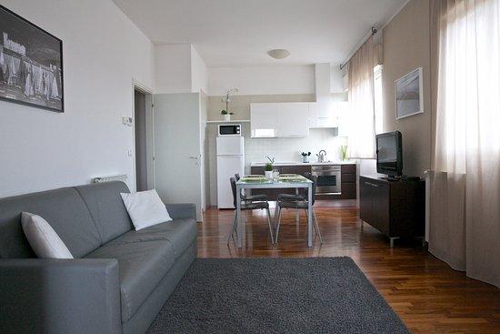 Soggiorno con angolo cottura dotato di stoviglie, tv e ...