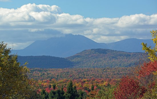 Patten, Мэн: Mt. Katahdin in Baxter State Park looms as the forest around it turns colors in the fall.