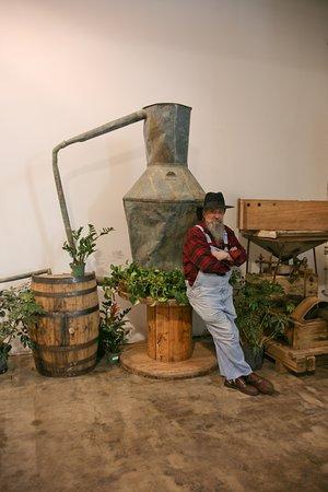 Dalton, GA: Master Distiller Raymond Butler next to his original illegal moonshine still