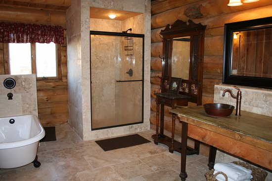 Nye, MT: Huge master bath has travertine stone shower, clawfoot tub, and double vanity.