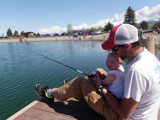 Bozeman, MT: Father and daughter enjoying warm morning fishing off the dock on Glen Lake, at EGRA