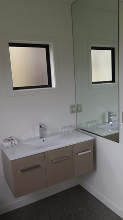 Garden Court Suites & Apartments: Lavatory with mirror on the right