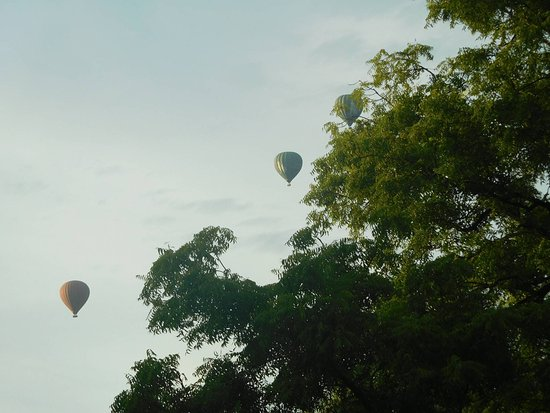 Nyaung U, Myanmar: View from balcony, hot air baloons early morning