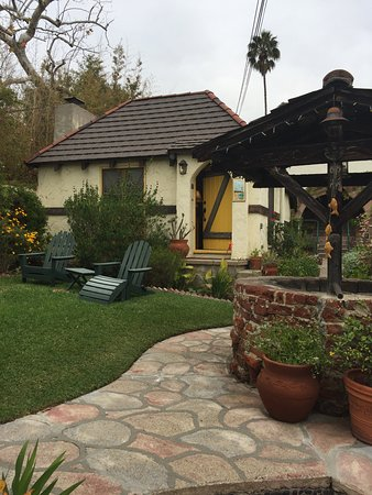 Manzanita Cottages: Yellow cottage from wishing well in common garden