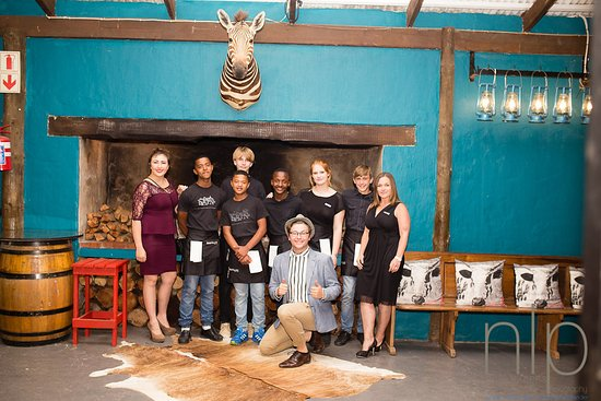 Mossel Bay, Südafrika: Our friendly staff in front of the massive fire place - the ideal winter venue!