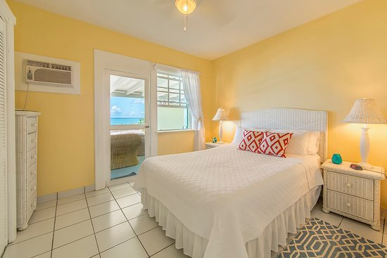 Crabtree Apartments: Bedroom of unit 1 with view of the sea and access to the private veranda and beach beyond.