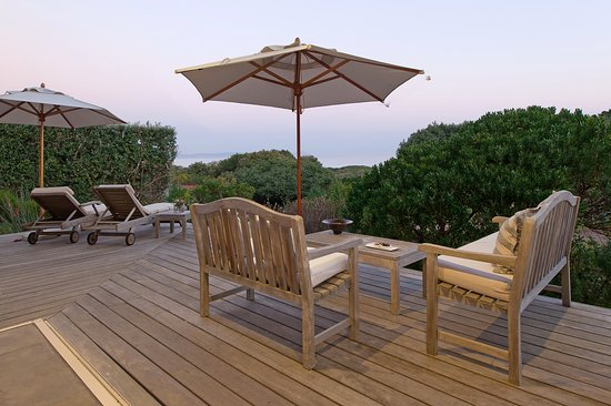 sea facing deck with seating and umbrellas picture of mosselberg