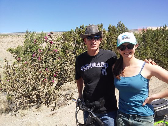 Cerrillos, NM: Me and my dad resting in front of a blooming Cholla cactus after our E-bike ride.