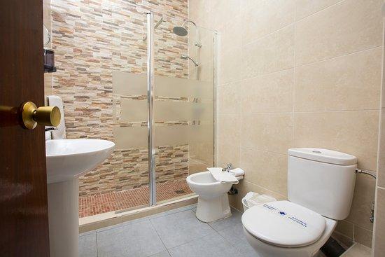 Cuarto de baño con ducha, secador de pelo, espejo de aumento ...