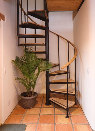 Alexander's Inn: Spiral Stairs in The Casita take you to the bedroom, with its king bed, surrounded by trees.